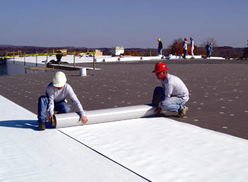 two commercial roofers working on a large roof
