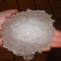 person holding hail stone as large as their hand
